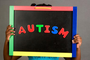 Girl holding chalk board that says Autism