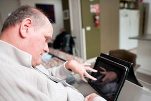 Man using an Ipad to communicate