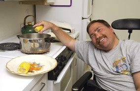 Man in a wheelchair cooking corn